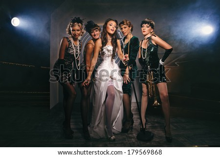 Young Singer bride with microphone and group of young women celebrating their friend`s forthcoming marriage - stock photo