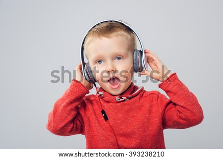 Young singer. Little boy with headphones. Child boy singing while listening to music  - stock photo