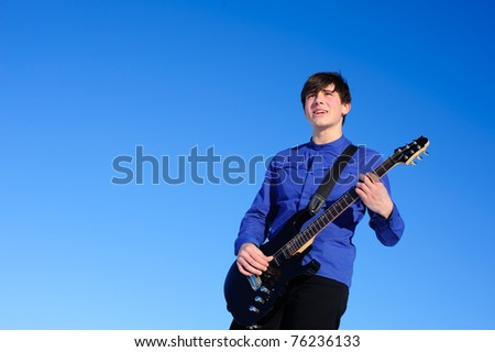 young singer with black guitar isolated on the blue sky - stock photo