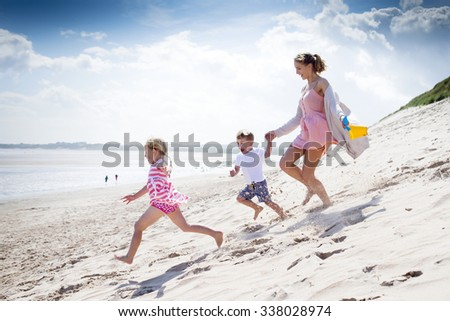 Young single parent family running down the sanddunes at the beach. - stock photo