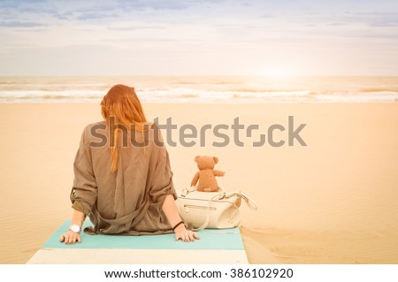 Young single woman sitting at beach with teddy bear looking at the sea - Solitude and loneliness concept with imaginary friendship and melancholic feelings - Warm vintage filter with enhanced sunshine - stock photo