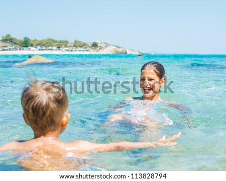 Young sister and brother playing in the transparent sea - stock photo