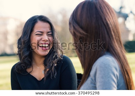 Young sisters having fun together in the park. - stock photo