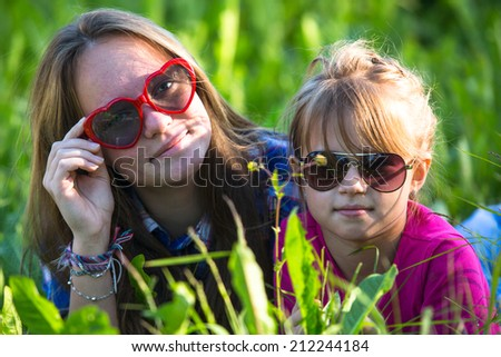 Young sisters lying in the grass. - stock photo