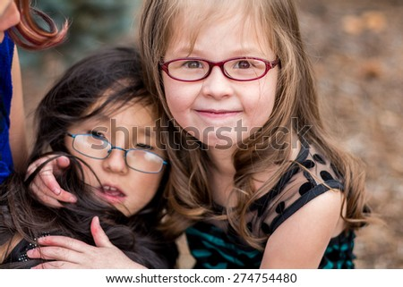 Young sisters playing outside together at a park in Reno, Nevada, USA. - stock photo