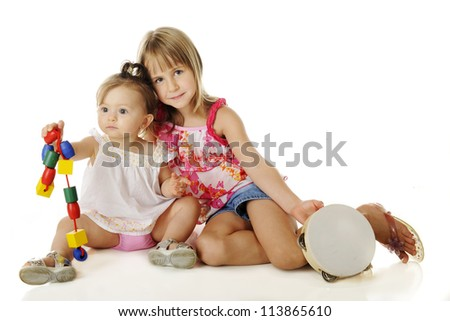 Young sisters playing together.  The older one stops for a moment to pose with the baby.  On a white background.