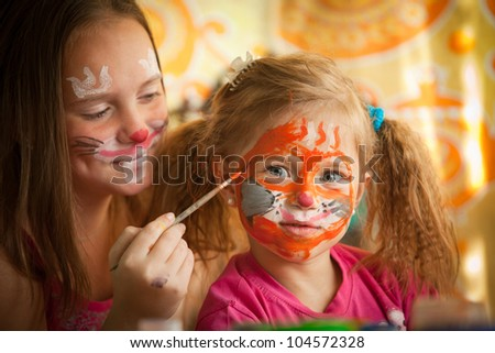 Young sisters playing with painting. - stock photo