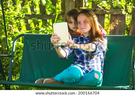 Young sisters shoot selfie on a tablet PC in the park. - stock photo