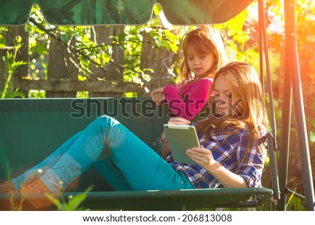Young sisters with a tablet PC, in the park. - stock photo