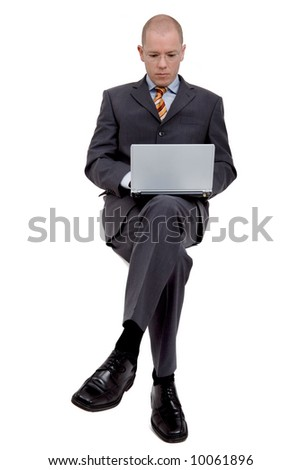 Young (sitting) businessman is working with a notebook. Full isolated studio picture - stock photo