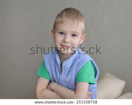 Young  sitting on sofa looking at camera on gray background - stock photo