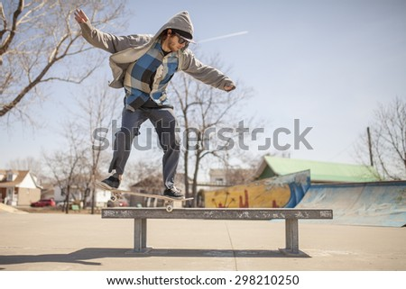 Young skateboard enthusiast in skatepark doing a nose grind