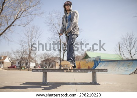 Young skateboard enthusiast in skatepark during day time - stock photo