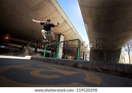 Young Skateboarder doing a Crooked Grind trick on a Rail - stock photo