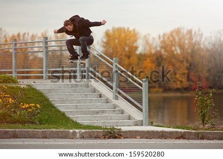 Young Skateboarder doing a Ollie down the stairs - stock photo