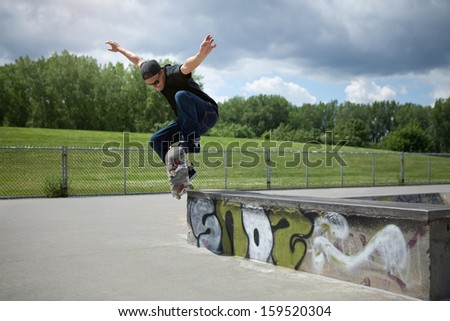 Young Skateboarder doing a Wallie in a skatepark - stock photo