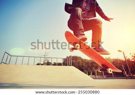 young skateboarder legs skateboarding at skatepark - stock photo