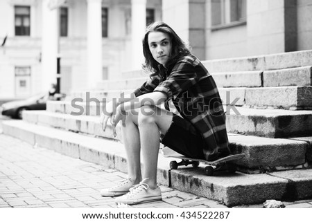 Young skateboarder sitting on the stairs
