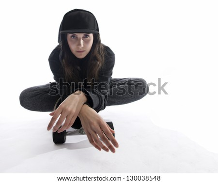 Young skater girl sits on her skateboard as she leans over the front edge of her board. - stock photo