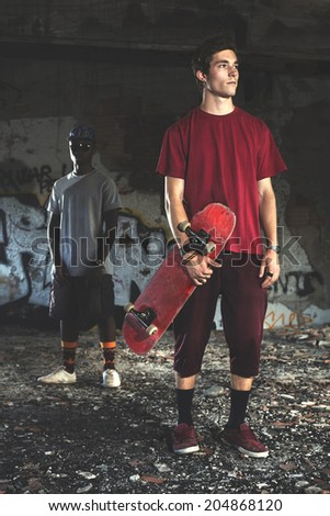 Young skater holding his skills in an urban place - stock photo