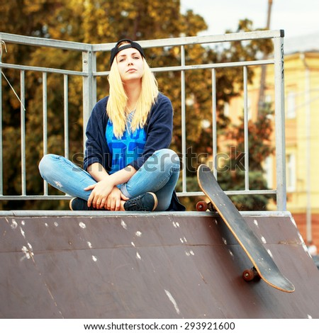 young skater sport girl with blond hair sitting and relaxing on top of hill with skateboard in skate park. Sunny autumn urban photo - stock photo