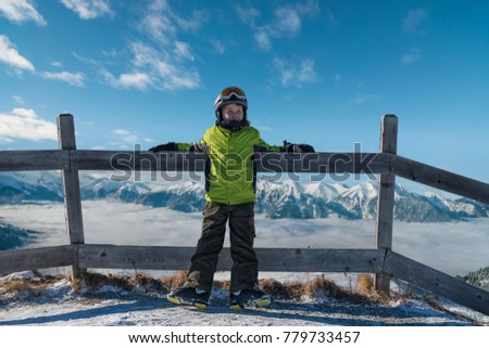 Young skier standing on ski track looking on alps