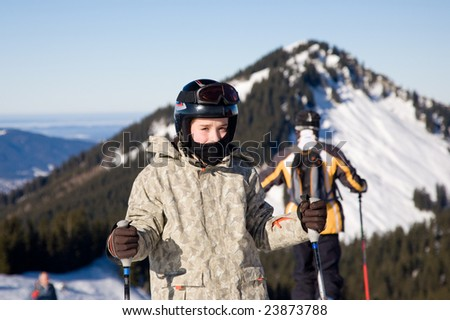 young skier standing with sticks and wearing helmet