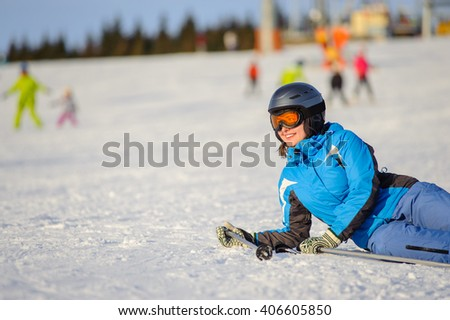 Young skier woman in blue ski suit orange goggles and helmet lying on the snow at ski resort on a sunny day. Ski vacation. - stock photo