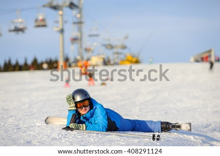 Young skier woman in blue ski suit orange goggles and helmet lying on the snow on a sunny day against ski-lift at ski resort. Winter vacation. - stock photo