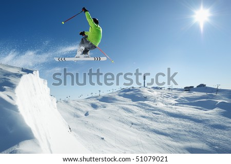 Young skiing man - skier at jump in beautiful alpen snow paradise - stock photo