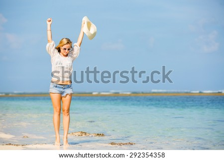 Young skinny caucasian girl at the beach waving with white hat over blue sky and pure ocean water on background. Travel, vacation, holidays, paradise concept, copyspace - stock photo