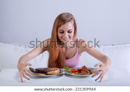 Young skinny girl binging on lots of food - stock photo