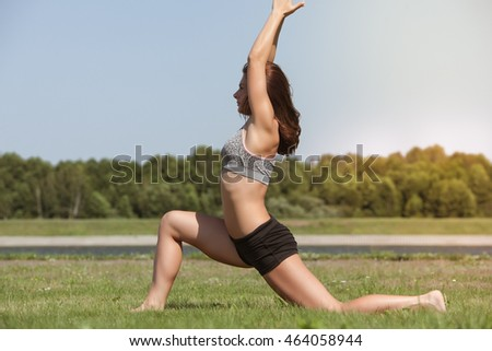 Young skinny girl does exercise on the grass.