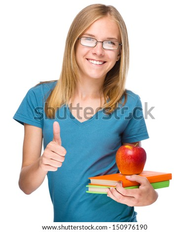 Young skinny student girl is holding exercise books and apple while showing thumb up gesture, isolated over white - stock photo