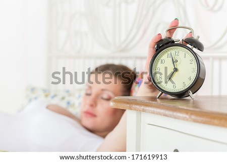 Young sleeping  pregnant woman and alarm clock in the bedroom.  Selective focus on a alarm clock.