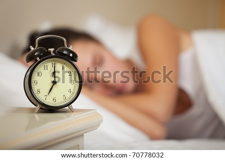 Young sleeping woman and alarm clock in bedroom at home. - stock photo