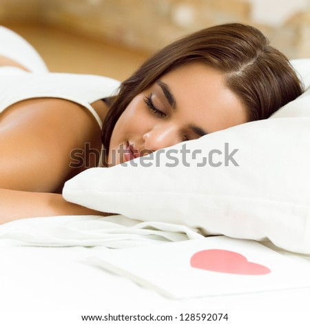 Young sleeping woman with valentine card on bed