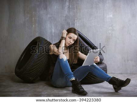 young, slender girl is sitting near the tires and looking at the plate against the background of gray concrete wall.