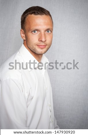 Young slightly smiling man in white shirt over gray background. Studio portrait  - stock photo