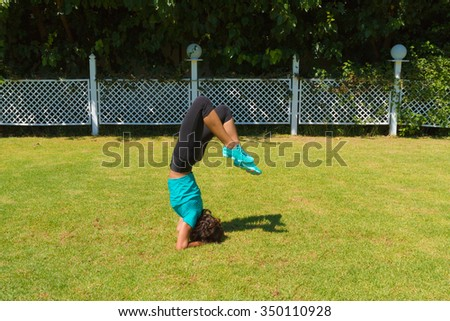 Young slim athletic woman in sportswear, doing handstands on the grass in the summer. Healthy lifestyle and fitness concept.