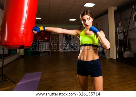 Young slim athletic woman is engaged in boxing. wear gloves next to the punching bag. dressed in a sports shirt and shorts, sneakers on his feet, arms boxing bandages - stock photo