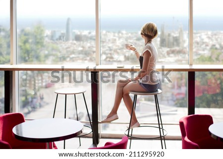 Young slim beautiful girl sits on a high bar stool in a cafe with stunning panoramic views of Barcelona. Siesta break with a cup of fragrant cappuccino - stock photo
