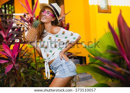 young slim beautiful stylish hipster woman in straw hat and pink sunglasses holding pineapple, smiling funny, happy summer, yellow wall background, denim shorts, cool t-shirt, trendy outfit, tropic