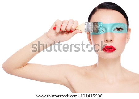 Young slim beautiful woman painting on her face,over white background - stock photo