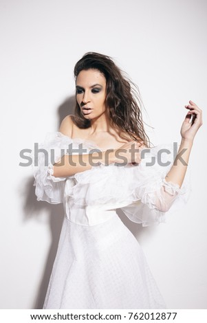 young slim brunette girl in white wedding dress. creative makeup and long hair. clear skin and healthy complexion. emotional portrait. posing in Studio on a white textured background