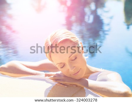 Young slim fit tanning woman having fun near pool - stock photo