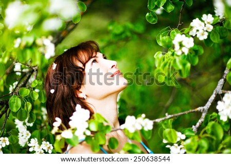 Young slim girl enjoying blooming apple tree.  - stock photo