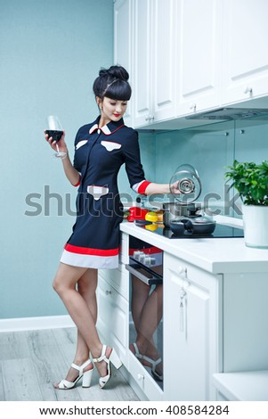 Young slim girl in the kitchen. The girl is drinking wine and preparing dinner. Household chores. - stock photo
