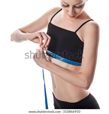 Young slim girl measures the volume of the breast. Girl dressed in sportswear. The concept of of losing weight and wholesome food.