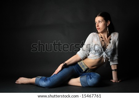 young slim girl sitting on the floor over black background - stock photo